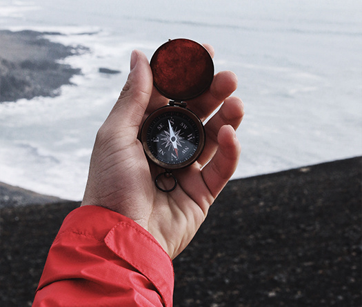 Hand holding a compass with view of the ocean to show preparing future-ready students to be engaged and global citizens