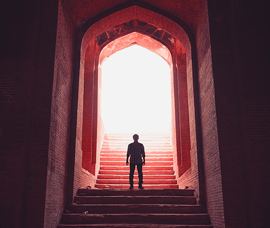 Person standing on stairs with a giant arch and light behind him to illustrate interintstutional partnerships for students at McGil