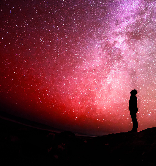 Person looking up at sky full of starts to illustrate McGill focus on breaking down barriers to research to understand the universe
