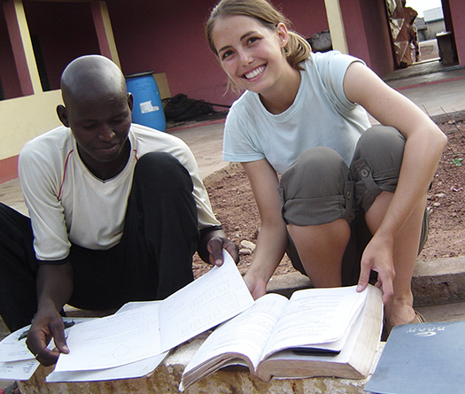 A McGill student doing experiential learning in Africa, looking at books with a young man