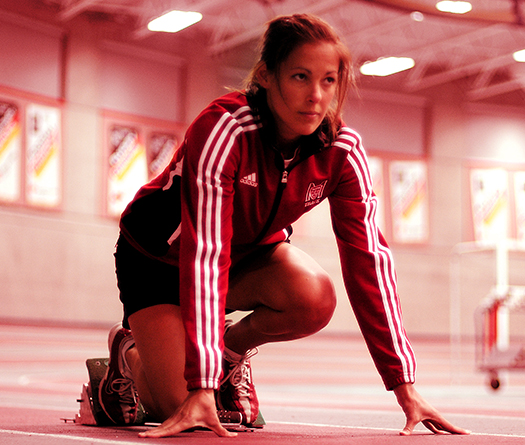 McGill student track athlete in starting position for a competitive run in a McGill athletic facility